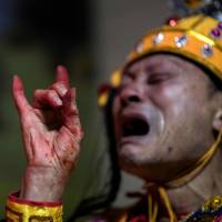 A villager dressed as a local sea deity cries as he prays after a procession in the village of Fuye on Nanri island in China's Fujian province Monday. | AFP-JIJI