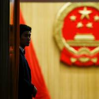 A security staff member keeps watch at the entrance to the assembly hall after the fourth plenary session of the National People's Congress at the Great Hall of the People in Beijing on Tuesday. | REUTERS