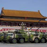 Chinese military vehicles carrying DF-21D anti-ship ballistic missiles, potentially capable of sinking a U.S. Nimitz-class aircraft carrier in a single strike, drive past Tiananmen Gate in Beijing during a military parade commemorating the 70th anniversary of the end of World War II in September 2015. | AP