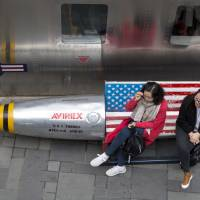 Chinese women sit outside an apparel store in Beijing on Friday, when China announced $3 billion in potential tariffs on U.S. goods. | AP