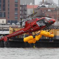 The wreckage of a chartered Liberty Helicopters helicopter that crashed into the East River is hoisted from the water in New York Monday. | REUTERS
