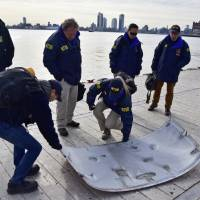 Investigators examine part of a helicopter Monday that crashed into New York's East River on Sunday evening. The pilot was able to escape the crash after the aircraft flipped upside down in the water, killing the five passengers on board. | NTSB / VIA AP