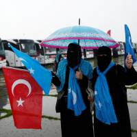 Activists wave Turkish and East Turkestan flags as they wait to take part in the International Conscience Convoy, which aims to reach the Turkish-Syrian border on the International Women's Day to raise awareness about the plight of Syrian women, in Istanbul Tuesday.   REUTERS