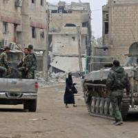 Syrian government forces' armored infantry fighting vehicles (IFVs) and trucks drive past damaged buildings down a street in the eastern Ghouta town of Hazzeh on the outskirts of the Syrian capital Damascus on Wednesday in the direction of the rebel-held town of Douma. | AFP-JIJI