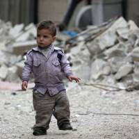 A Syrian child roams the streets Wednesday in the town of Hazzeh in eastern Ghouta. | AFP-JIJI
