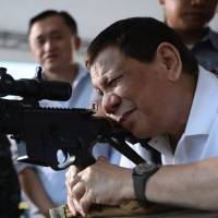 Philippine President Rodrigo Duterte fires a few rounds with a sniper rifle during the opening ceremony of the National Special Weapons and Tactics (SWAT) Challenge in Davao City, on the southern Philippine island of Mindanao, on March 1. | AFP-JIJI