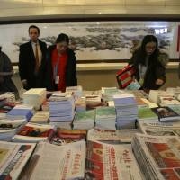 Journalists and others browse through newspapers and journals displayed at the media center for China's National People's Congress (NPC) in Beijing on Tuesday. | AP