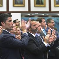 Rep. Jose Oliva (front), who shepherded a gun control bill through the Florida House, and other House members applaud Marjory Stoneman Douglas High School parent Andrew Pollack, whose daughter Meadow was killed in the shooting at the school, on Wednesday in Tallahassee. | AP