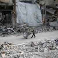 A man pushes a cart past damaged buildings at the besieged town of Douma, eastern Ghouta, Damascus, Monday. | REUTERS