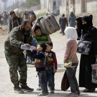 A member of the Syrian government forces helps children drink from a water jug during a civilian evacuation from the eastern Ghouta enclave through the regime-controlled corridor opened by government forces in Hawsh al-Ashaari, east of the enclave town of Hamouria on the outskirts of the capital Damascus on Thursday. | AFP-JIJI