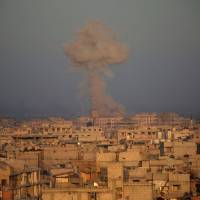 Smoke billows in Zamalka, in the Syrian rebel enclave of eastern Ghouta on the outskirts of Damascu, during reported shelling by Syrian government forces on Monday. | AFP-JIJI