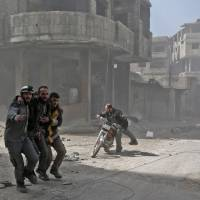 Volunteers from the Syrian civil defense help a man in Hamouria during Syrian government shelling on rebel-held areas in the eastern Ghouta region on the outskirts of the capital Damascus on Tuesday.   AFP-JIJI