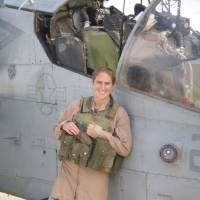 This handout photograph obtained March 4 shows Cobra helicopter pilot of the U.S. Marine Corps Kyleanne Hunter standing before the Cobra helicopter, 2007-2008 in Iraq. A group of U.S .military veterans, including Kyleanne Hunter, is calling for changes to permissive American firearms regulations in the wake of recent mass shootings, bringing their knowledge of weapons and war — and accompanying credibility — to the contentious debate over countering gun violence. | KYLEANNE HUNTER / STR / VIA AFP-JIJI