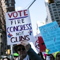 A demonstrator holds a sign on New York's 6th Avenue during the March For Our Lives on Saturday. | BLOOMBERG