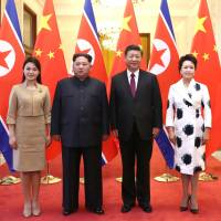 North Korean leader Kim Jong Un and his wife, Ri Sol Ju (left), pose for a picture with Chinese President Xi Jinping and his wife, Peng Liyuan, at the Great Hall of the People in Beijing in this picture released Wednesday. | REUTERS