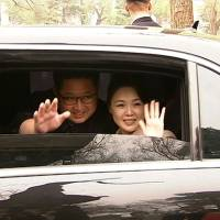 North Korean leader Kim Jong Un and his wife, Ri Sol Ju, wave goodbye as they depart by car following a meeting with Chinese President Xi Jinping in Beijing in this screenshot taken from footage released Wednesday. | AFP-JIJI