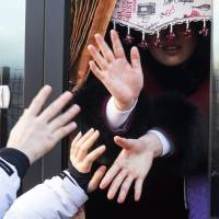 North Korean women's hockey players in a bus reach out to hold hands with their South Korean teammates on Feb. 26, at Olympic Village in Gangneung, South Korea, as they return to North Korea. | AP