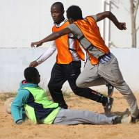 Cameroonian (orange) and Senegalese (yellow) African migrants, split into two teams, take part in a soccer match at the Libyan Interior Ministry's illegal immigration shelter in Tajoura on Feb. 28. | AFP-JIJI