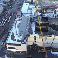 This Russian Emergency Situations Ministry photo taken on Mondayshows an aerial view of emergency services working at the scene of the multistory shopping center after Sunday's fire, in the Siberian city of Kemerovo. Russian officials say that fire escapes were blocked and a public address system was turned off at the mall. Witnesses reported no alarms and no staff to help them leave the Winter Cherry mall. | RUSSIAN MINISTRY FOR EMERGENCY SITUATIONS PHOTO / VIA AP