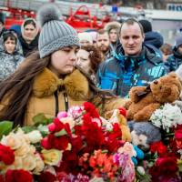 A woman lays flowers in tribute to the victims of the fire at the shopping center in Kemerovo, Russia, Monday. | AFP-JIJI