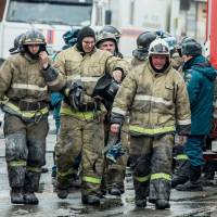 Russian emergency firefighters walk near a multistory shopping center in Kemerovo on Monday. At least 53 bodies have been recovered from a fire that swept through a busy shopping center in the industrial city in Siberia, Russian news agencies said Monday. | AFP-JIJI