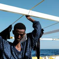 A 22-year-old Eritrean man is seen on the Proactiva Open Arms rescue ship after being rescued in the Mediterranean off Libya Sunday. | REUTERS