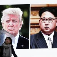 A woman walks by a huge TV screen in Tokyo on Friday showing U.S. President Donald Trump and North Korean leader Kim Jong Un.   AP