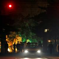 A Chinese military honor guard is seen marching away late Monday after a convoy of vehicles entered the Diaoyutai State Guesthouse, where top North Korean leaders have been known to stay on previous trips to Beijing. | AP