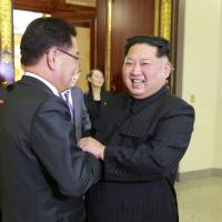 North Korean leader Kim Jong Un greets a member of the South Korean delegation sent by President Moon Jae-in ahead of a group dinner in this photo released Tuesday. | REUTERS
