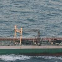 The Belize-flagged tanker Wan Heng 11 is seen on Feb. 13 after carrying out what Japan's Defense Ministry suspects was a banned 'ship-to-ship' transfer with a North Korean ship in the East China Sea. The tanker's owner has links to Hong Kong. | AP