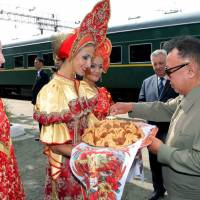 North Korea's then leader Kim Jong Il is welcomed by Russian women in traditional dress at the Bureya station in Russia's Amur region in August 2011. | KCNA / VIA AFP-JIJI