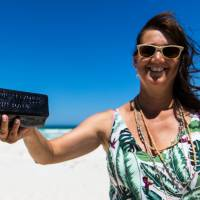 Tonya Illman holds a bottle with an almost 132-year-old message that she found near Wedge Island on Australia's west coast in January. | AFP-JIJI