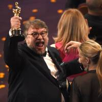 Guillermo del Toro, winner of the award for best director for 'The Shape of Water,' celebrates in the audience at the Oscars on Sunday at the Dolby Theatre in Los Angeles. | CHRIS PIZZELLO/INVISION/AP