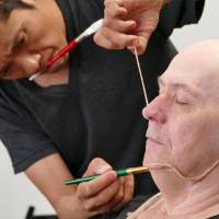 Kazuhiro Tsuji applies make-up to actor Gary Oldman as he transforms him into British wartime leader Winston Churchill for the film 'Darkest Hour.' | KYODO