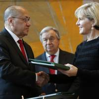 East Timorese Minister of State Hermenegildo Augusto Cabral Pereira shakes hands with Australian Foreign Minister Julie Bishop after the two signed a treaty that draws a maritime border between the neighbors on Tuesday at United Nations headquarters. | AP