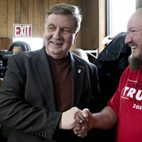 Rick Saccone, Republican candidate for the U.S. House of Representatives, meets an attendee wearing a Donald Trump campaign T-shirt during an event with volunteers and service members at the Blaine Hill Volunteer Fire Department in Elizabeth, Pennsylvania, on Monday. | BLOOMBERG