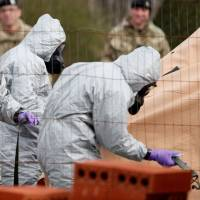 British Military personnel wearing protective coveralls work to remove a vehicle connected to the March 4 nerve agent attack in Salisbury, from a residential street in Gillingham, southeast England on Wednesday. | AFP-JIJI