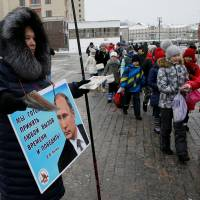 An activist distributes electoral materials in support of presidential candidate President Vladimir Putin in central Moscow on Thursday. The placard reads: 'We are ready to take any challenge of time and win V.V. Putin.' | REUTERS