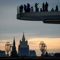 People enjoy the view from a pedestrian bridge in the Zaryadye Park, with the Kremlin's towers and the Russian Foreign Ministry headquarters seen in the background, in Moscow on Tuesday. | AFP-JIJI
