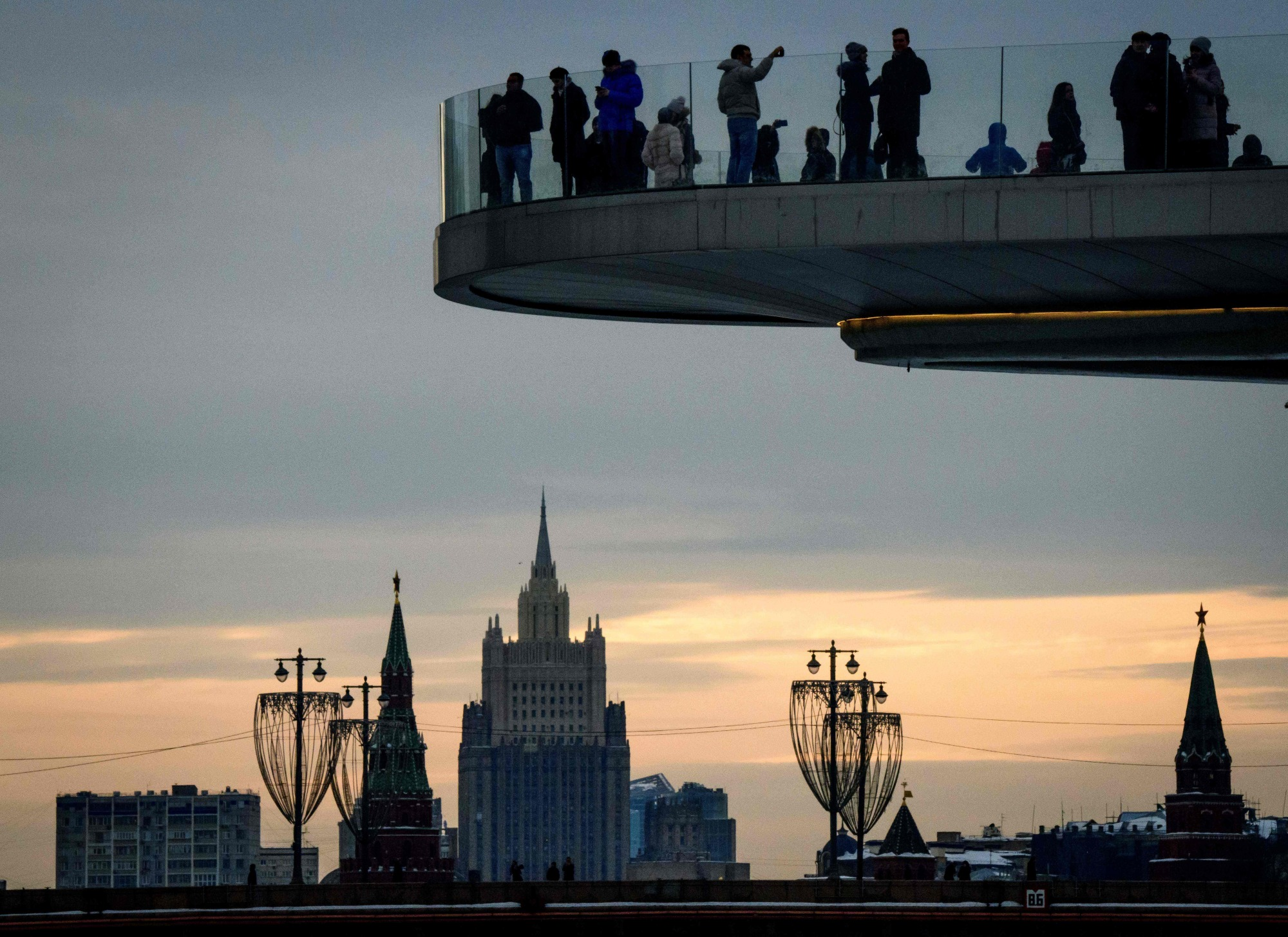 People enjoy the view from a pedestrian bridge in the Zaryadye Park, with the Kremlin's towers and the Russian Foreign Ministry headquarters seen in the background, in Moscow on Tuesday.   AFP-JIJI