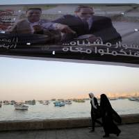 Women walk along the shoreline in front of banners with Egypt's President Abdel Fattah al-Sisi during preparations for the presidential election in Alexandria, Egypt, Sunday. | REUTERS