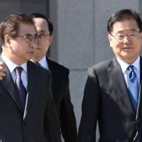 Chung Eui-yong (left), head of the South Korean presidential National Security Office, and Suh Hoon, chief of the South's National Intelligence Service, talk before boarding an aircraft as they leave for Pyongyang at a military airport in Seongnam, south of Seoul, on Monday. | POOL / VIA REUTERS