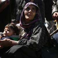A Syrian woman and a child are seen in the village of Qalaat al-Madiq, some 45 kilometers northwest of the central city of Hama, on Monday, as evacuations from eastern Ghouta continue following a deal that was announced earlier in the week. | AFP-JIJI