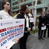 Plaintiffs Cathrine Schmid (second left) and Conner Callahan (second right) listes with supporters during a news conference in front of a federal courthouse following a hearing there Tuesday in Seattle. U.S. District Judge Marsha Pechman says she won't immediately consider President Donald Trump's new policy banning transgender people from serving in the military. Pechman is one of four federal judges who have issued orders blocking Trump's decision last year to overturn an Obama-era directive allowing transgender troops to serve openly. | AP