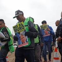 Police officers stand gua.rd while demonstrators take part in a protest over U.S President Donald Trump's migration policies on the Mexican side of the Mexico-U.S. border in Tijuana, Baja California state, ahead of Trump's arrival for the inspection of prototypes of the border wall, on the outskirts of San Diego, California, Tuesday. | AFP-JIJI