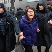A woman is detained by riot police during a Women's Day rally in Ankara Sunday. | REUTERS