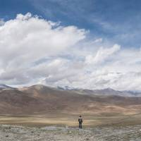 A man looks out over the China-Pakistan Friendship Highway and the Karakoram mountain range near Tashkurgan in China's western Xinjiang province, near the China-Pakistan border, last June. | AFP-JIJI