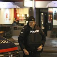 A police officer stands in front of a Japanese restaurant after several people were wounded in a knife attack on the streets of Vienna Wednesday. | AP