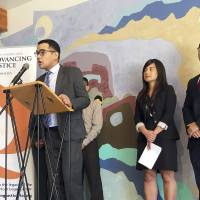 Christopher Lapinig, at podium, an attorney at Asian Americans Advancing Justice-Los Angeles, is among lawyers for Vietnamese immigrants suing the federal government over their detention by U.S. immigration authorities, at a news conference in Santa Ana, California, Wednesday. The lawyers say immigrants who arrived from Vietnam before the country resumed diplomatic relations with the United States in 1995 are not subject to a repatriation agreement between the countries, and thus their detention isn't legal. Also seen are Phi Nguyen, litigation director at Asian Americans Advancing Justice-Atlanta (center) and attorney Tuan Uong. | AP