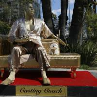 A dog named 'Sassi' sits next to a golden statue of a bathrobe-clad Harvey Weinstein, seated atop a couch on the sidewalk along Hollywood Blvd., in Los Angeles Thursday. The piece, titled 'Casting Couch,' is a collaborative effort between a Los Angeles street artist known as Plastic Jesus and Joshua 'Ginger' Monroe, creator of the nude Donald Trump statue. Plastic Jesus said the piece was meant to shine a light on the entertainment industry's sexual misconduct crisis and the disgraced movie mogul's prominent role in it. | AP